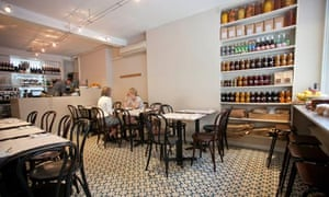 Tables and chairs with shelves of jars at Honey and Co