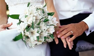 Bride's hand with flowers holding groom's hand