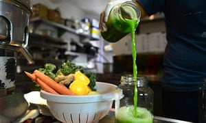 Green juice being poured into a jar next to fresh vegetables