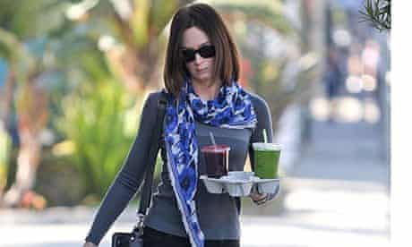 Emily Blunt walking in Los Angeles holding two juices