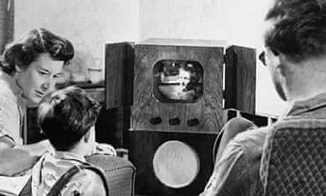A family huddled around a TV in the 1950s