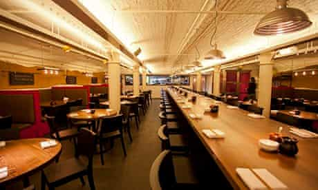 Huge communal table in Flesh & Buns, with booths on the side