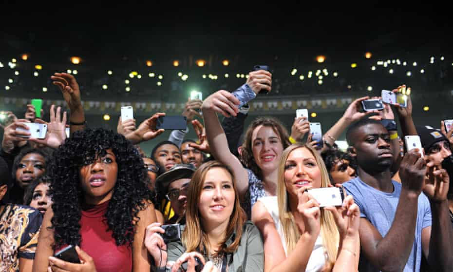 Phone-wielding fans record a concert at London's   Hammersmith Apollo.