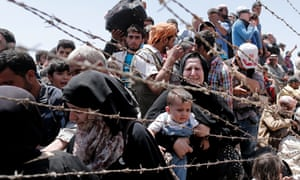 Syrian refugees wait to cross the border into Turkey.  Samar Yazbek crossed the other way…