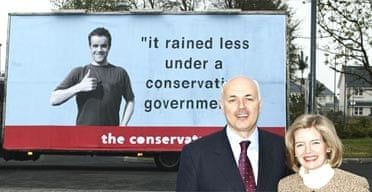 Iain Duncan Smith and his wife pose in front of a spoof election poster