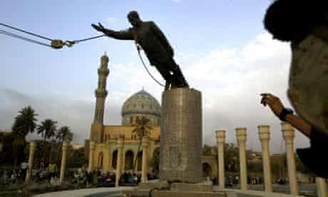 A US marine watches a statue of Saddam Hussein being toppled in Baghdad on April 9 2003. Photograph: Jerome Delay/AP