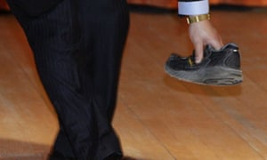 A security guard picks up a shoe that was thrown at Chinese premier Wen Jiabao on February 2 2009