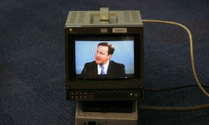 David Cameron appears on a monitor at the Conservative party conference during a TV interview