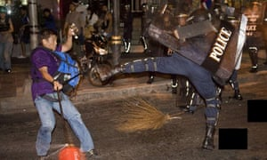 A pro-governement protester clashes with a riot policeman on Bangkok's Silom Road