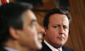 David Cameron looks towards the French PM, François Fillon, during a press conference at No 10