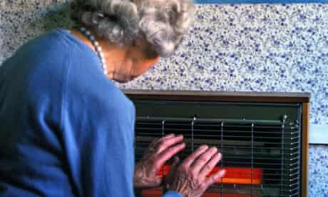 Elderly woman warms her hands on an electric heater