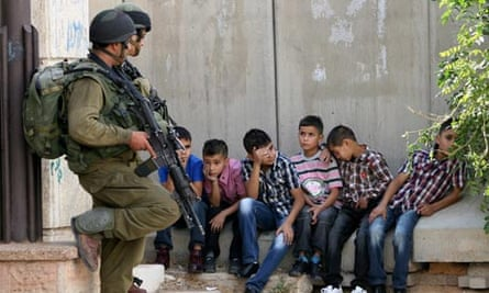 Israeli soldiers guard Palestinian children