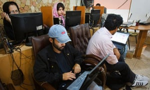 Customers use computers at an internet cafe in Tehran