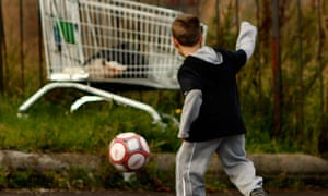 Young boy playing football in the street