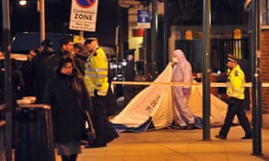 Police and forensics officers attend the scene of a fatal shooting at Turnpike Lane, London
