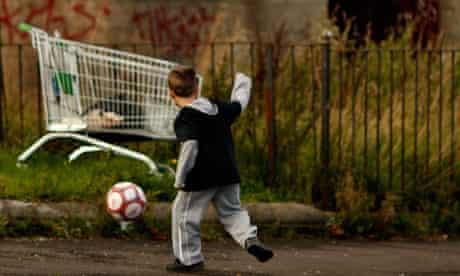 A young boy plays football in a rundown street