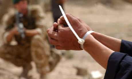 A suspected Iraqi soldier is held with flexi cuffs after surrendering