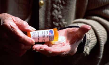 Elderly woman opening bottle of cholesterol pills medication