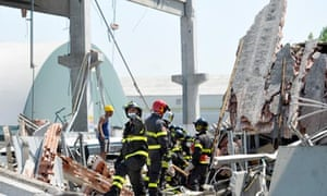 Firefighters search the debris of a collapsed factory in Mirandola, northern Italy