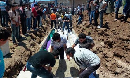People gather at a mass burial for victims killed in Houla
