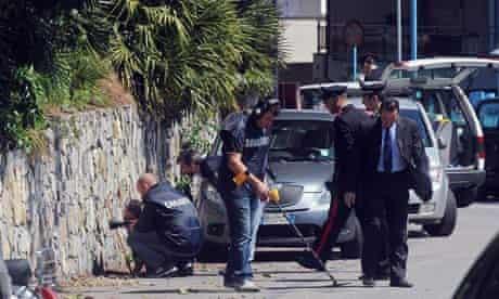 Police officers investigate the site where Roberto Adinolfi was shot