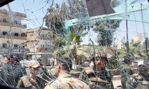 Syrian army soldiers are seen through a damaged military truck window