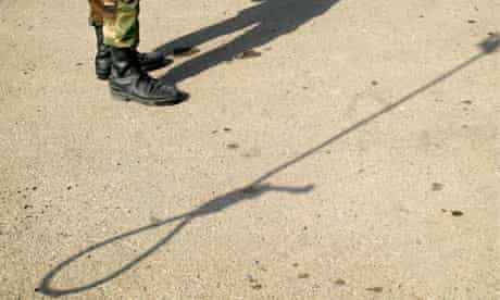Shadows of an Iranian policeman and a noose are seen on the ground before an execution