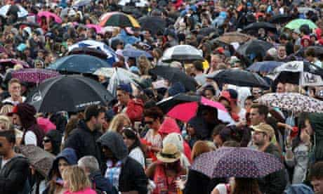 Umberellas go up during a rain storm at the Wireless Festival in Hyde Park