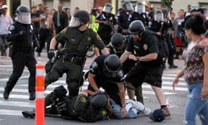 A protester is arrested by police officers from Orange County