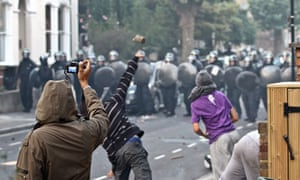 A youth films rioters throwing missiles at police during the riots in London last year