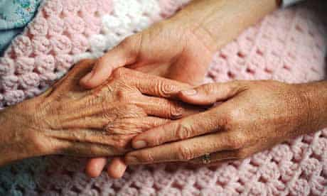 A caring geriatrician holds the hand of an elderly woman with arthritis