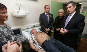 Gordon Brown meets staff at Brocklebank Health Centre, London, as patient John Brennan, 51, is given an ultrasound to check for aneurisms. Photograph: Lewis Whyld