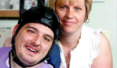 Simon Stevens, a disability consultant who has cerebral palsy, with his personal assistant Flora Lloyd at home in Coventry