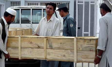 Afghan men carry coffins containing bodies of foreign aid workers who were killed while working for the New York-based International Rescue Committee