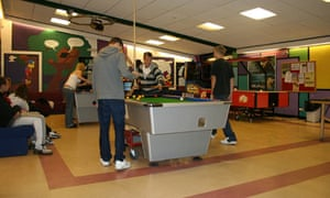 Teenagers playing pool in a youth club