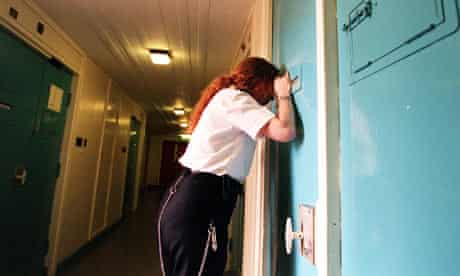A female prison officer checks on inmates