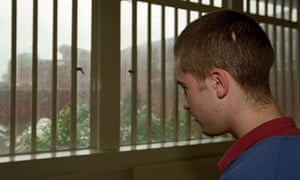 Young offender in a YoI gazes out of the barred window. Image shot 2006.