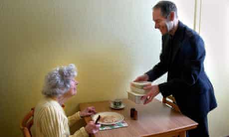 man giving elderly woman prepackaged meal Meals on wheels service