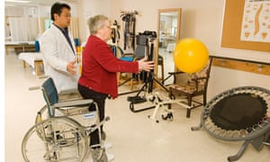 Physiotherapist helps a woman exercise after a stroke