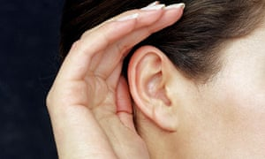 Woman cupping hand to her ear