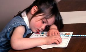 child who has fallen asleep over her school work