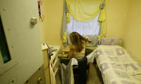 A female prisoner brushing her hair in her cell at Brockhill women's prison in Redditch