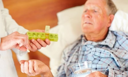 Old man in bed being given a pill by doctor