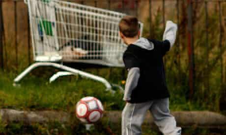 Child playing football in rundown area