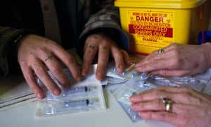 Sterile syringes being distributed to a drugs user as part of the needle exchange programme