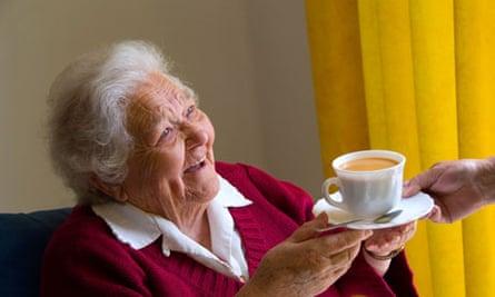 Older woman receiving a cup of tea