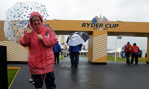 A woman walks out of the tented village as rain delays play on the third day of the Ryder Cup