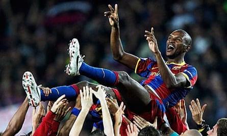 Barcelona's Eric Abidal is held aloft