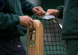 Wimbledon photo book: Staff sets up the net on Centre Court before the start of the Championships