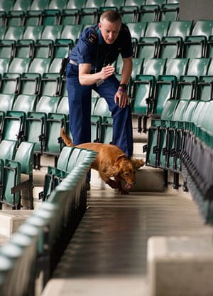 Wimbledon photo book: A policeman checks the seats on Court 1 with his sniffer dog